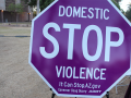 "a purple stop sign with the text ""Domestic STOP Violence; It Can Stop.AZ.gov Governor Doug Ducey ADOT"