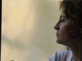 the profile of a woman's head as she looks through a window into the distance