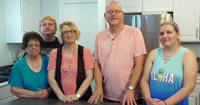 a group of people stand in a kitchen, posing for the camera