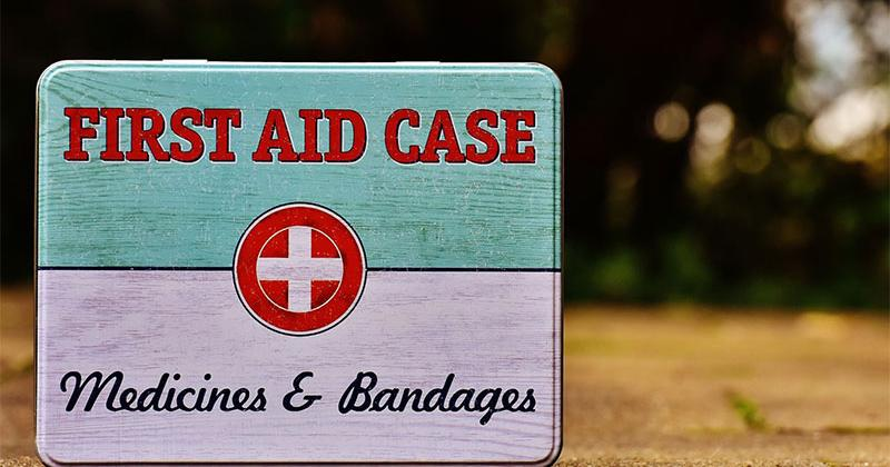a vintage tin first aid case; the words First Aid Case + Medicines & Bandages display on the lid