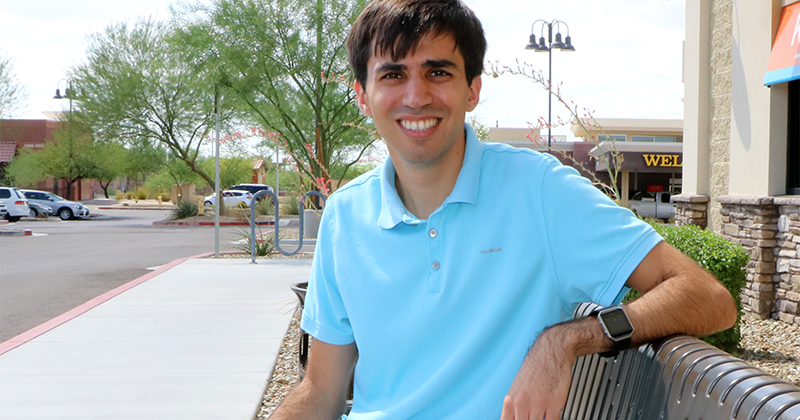a young man sits on a bench, smiling for the camera; in the background, there are cars in a parking lot surrounded by desert landscaping
