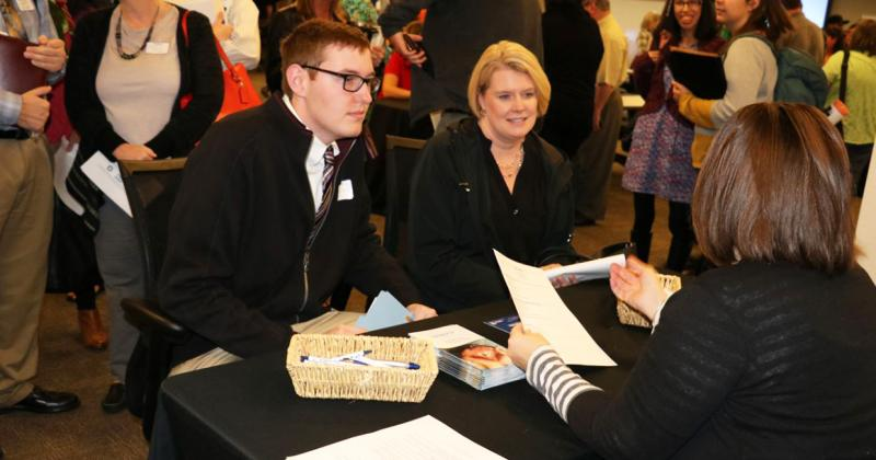 a professionally dressed young man and an older woman speak to another woman sitting across the table from them