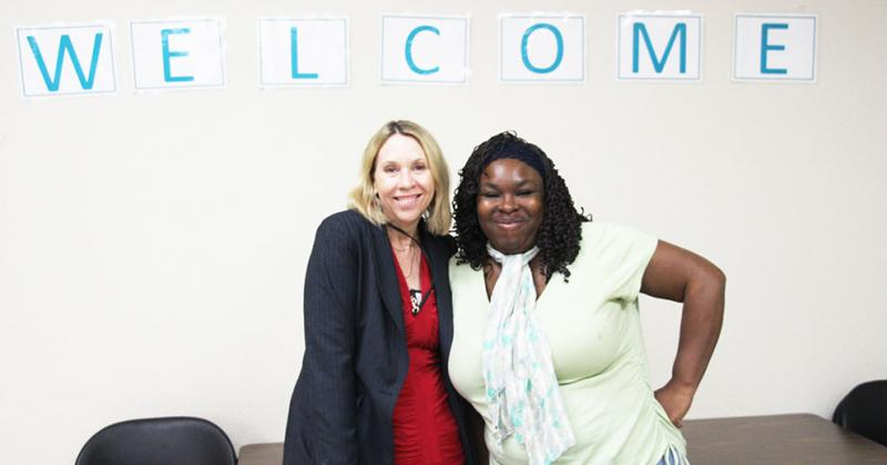 "Two women (Lisa DeForest and Oletha Hall) standing together under a sign that reads ""Welcome."""