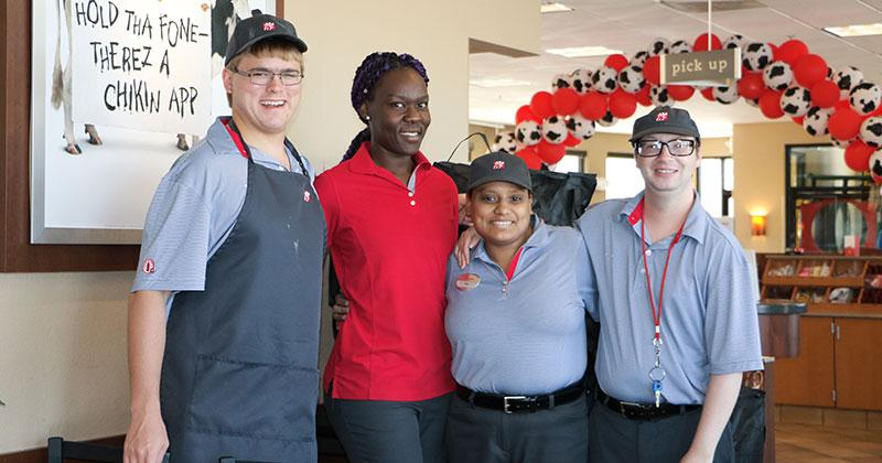 three restaurant employees pose for a photo