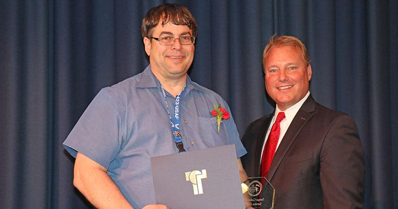 two men smile and pose for a photo; one holds a Community Service Award