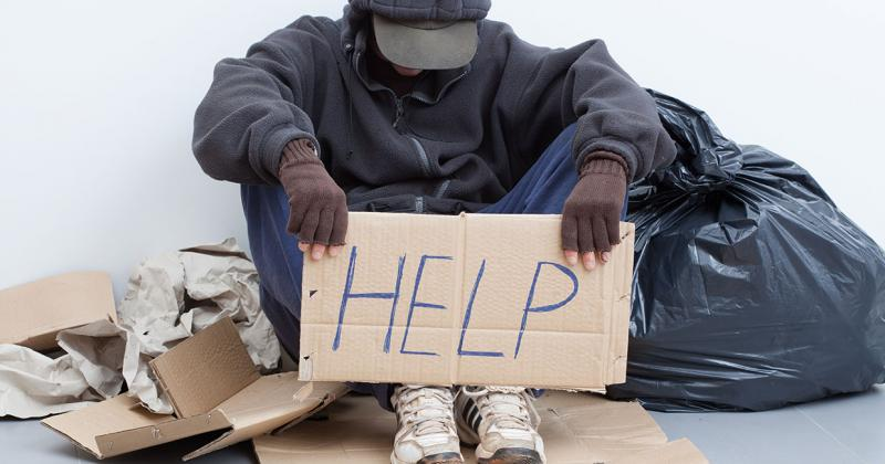 a homeless man sits on the sidewalk holidng a help sign