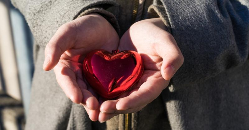 a shiny heart shaped figure sits on a persons cupped hands
