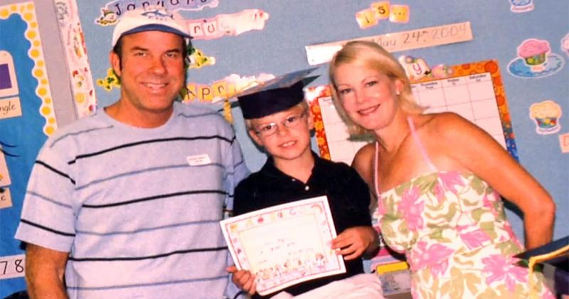 a young boy stands between his father and mother holding a certificate
