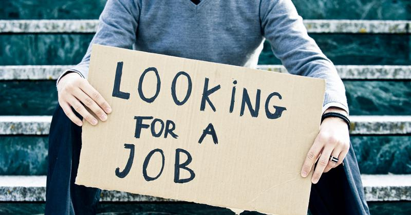 a young man holds a cardboard sign that reads Looking for a Job