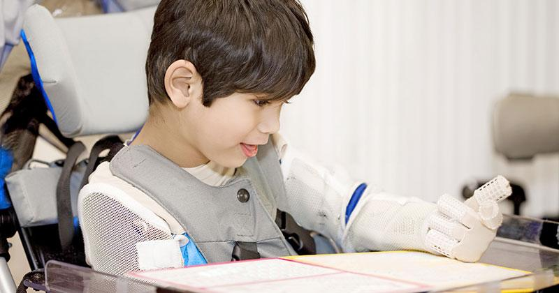 a boy in a wheelchair reading papers