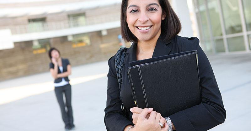 a smiling woman dressed in a business suit holds a leather bound folder