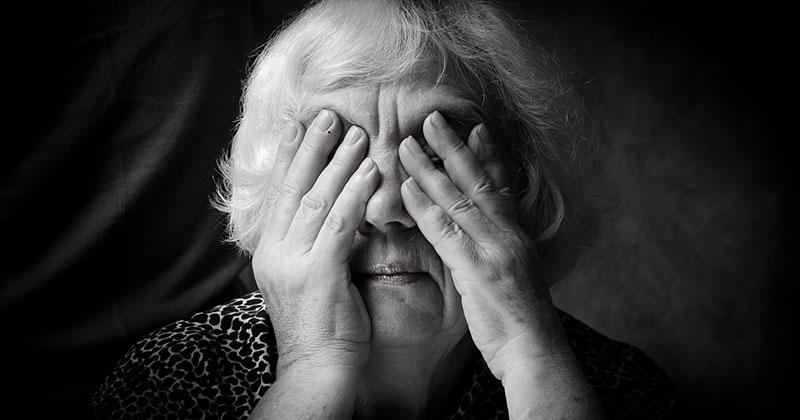elderly woman covering her face with her hands