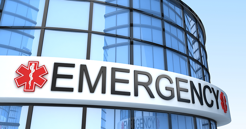 "a sign on a building reads ""EMERGENCY"""