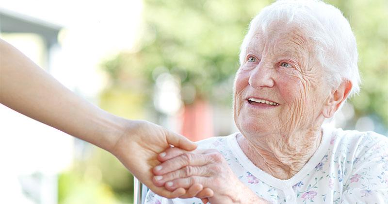 someone's hand helps a smiling elderly woman
