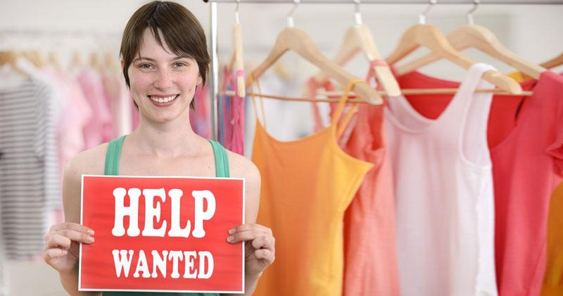 happy proud owner of store with help wanted sign