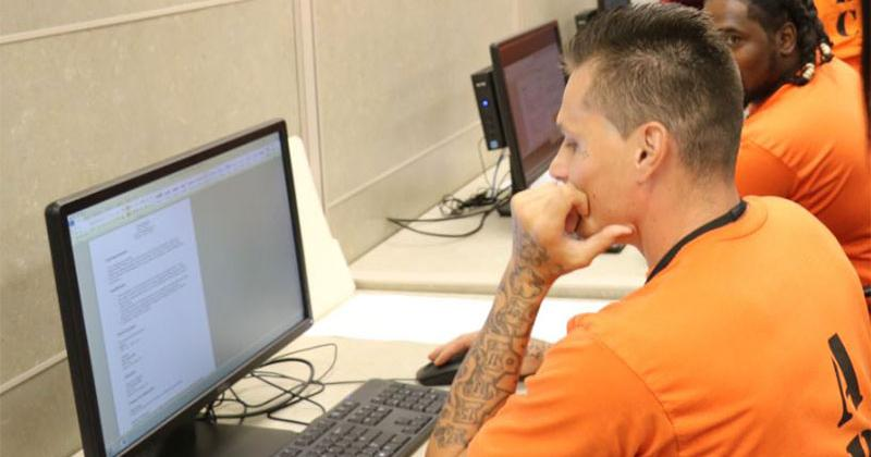 Inmates working on computers.