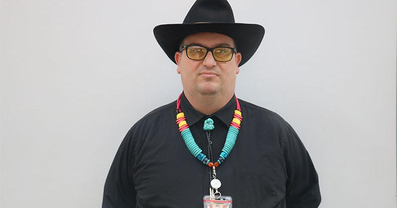 man in black shirt and cowboy hat standing against white wall