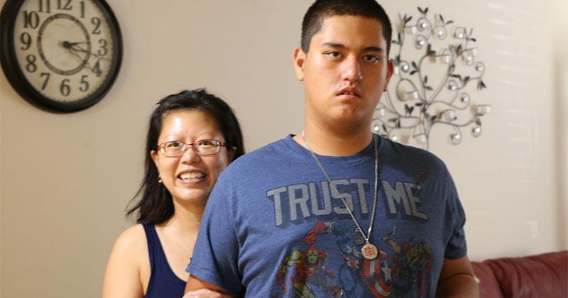With her hand on his arm, a mother stands behind her teenage son in their East Valley living room.