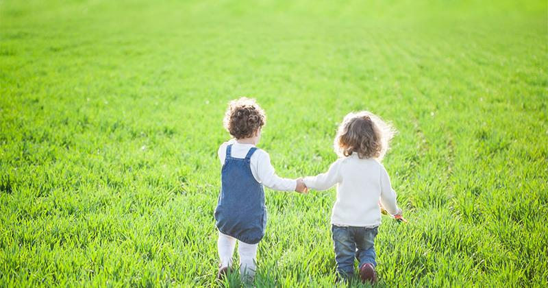 two toddler girls holding hands walk over a grassy field