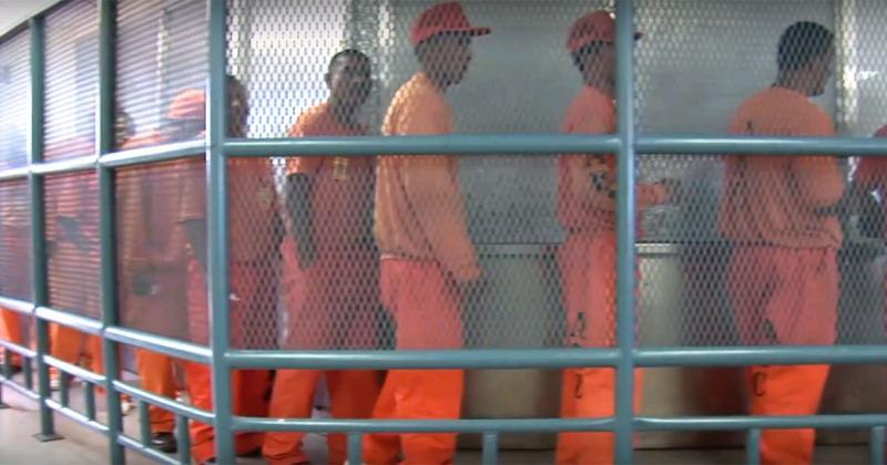 Men in orange uniforms waiting in line
