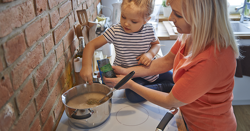 A woman stands before a cooking range holding a packet over a pot. A young girl sits nearby on a countertop, sprinkling brown powder into the pot.