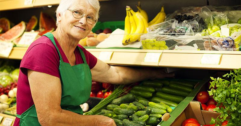 an older woman working in the produce section of a grocery store