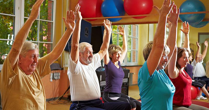 a group of older people sitting on exercise balls with their arms raised towards the ceiling