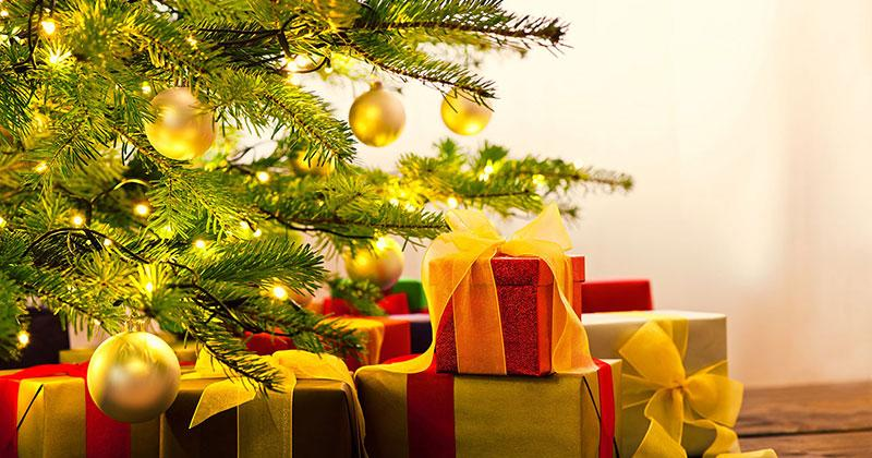 presents piled under a decorated pine tree