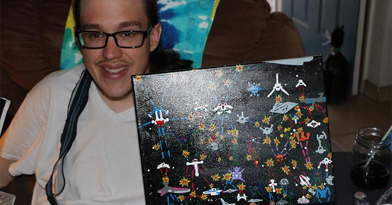 young man smiles, holding up a painting of alien spaceships
