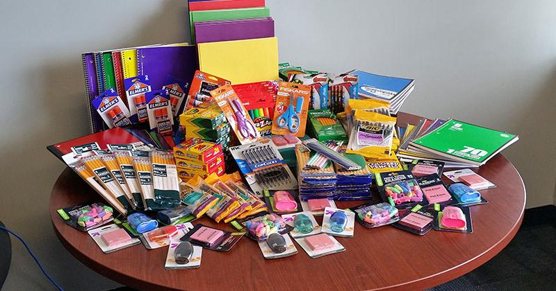 a variety of school supplies are pile on a table top