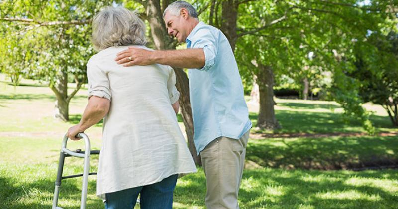 An older man guides a mature woman as she uses a walker during a walk through the park