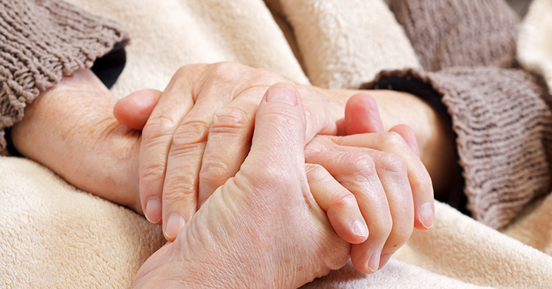 close up of a senior's hand clasping another senior's hands