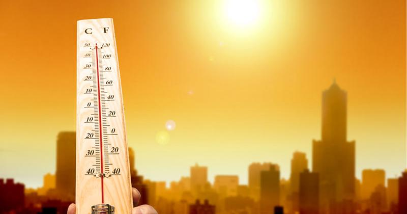 A thermometer shows 120 degrees Farenheit as the sun shines high above tall city buildings
