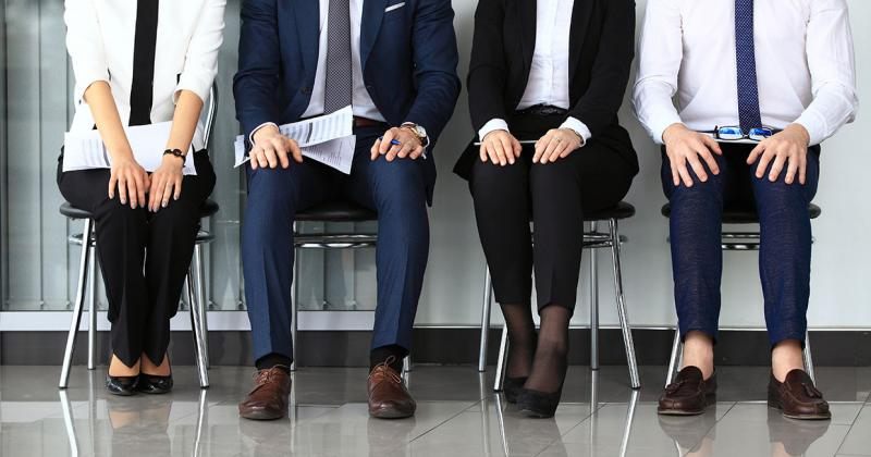 two men and two women dressed in business attire sit in a waiting room