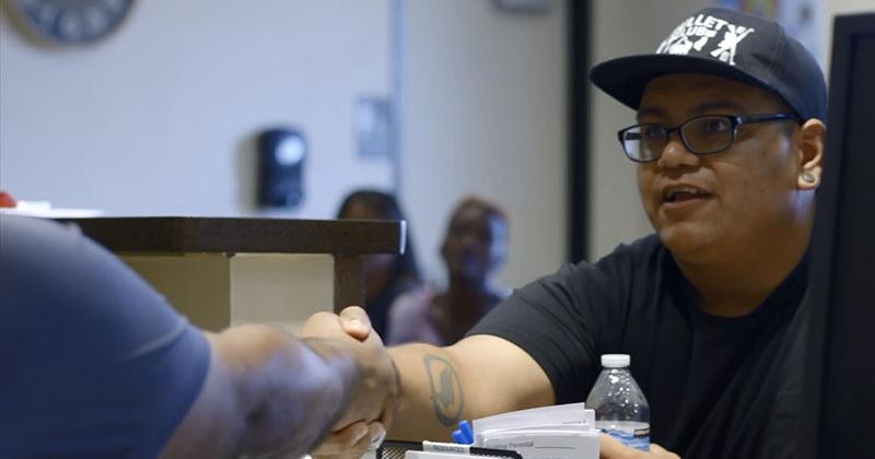 A man wearing a baseball cap and glasses shakes hands with another man who sits behind a desk. In the background, people sit in a waiting area.