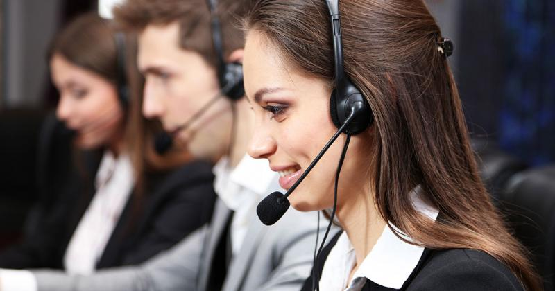 two women and a man sit side by side speaking into their telephone headsets