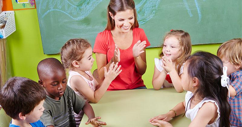 Adult woman and children sit at table in school setting.