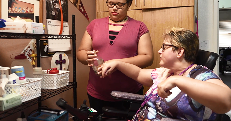 A woman stands holding a jar in her hand while a woman in a wheelchair reads the label.