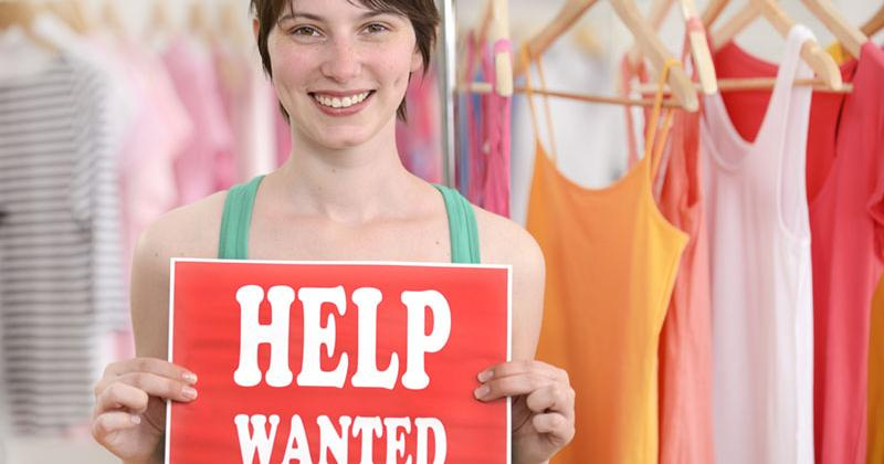 "a woman stands inside a clothing store holding a sign that reads ""Help Wanted"""