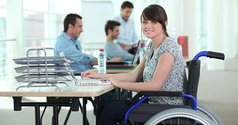 woman in wheelchair sits at desk