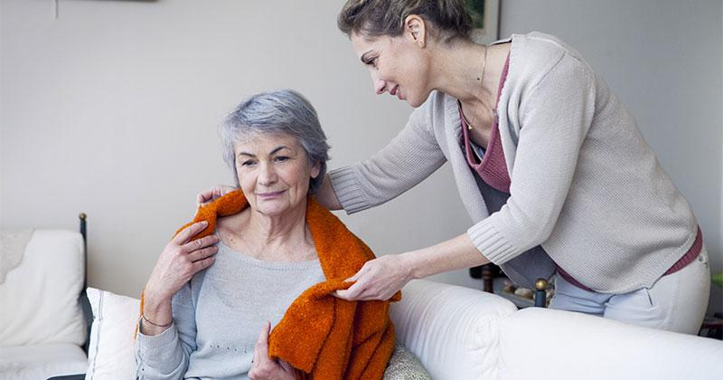 a smiling woman is wrapping a blanket around an older woman's shoulders