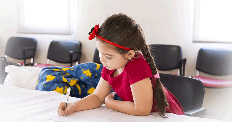 a young girl sits a table, writing on a sheet of paper