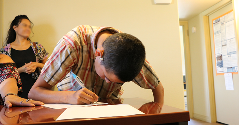 a young man signs a document on a table top