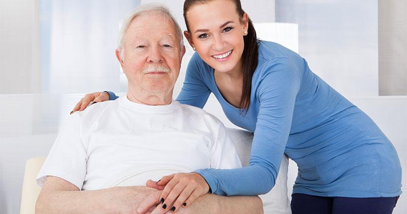 a young woman embraces a bed ridden older man