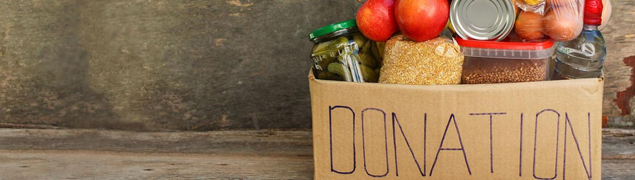 "a cardboard box filled with nonperishable food items; the side of the box reads ""donations"""