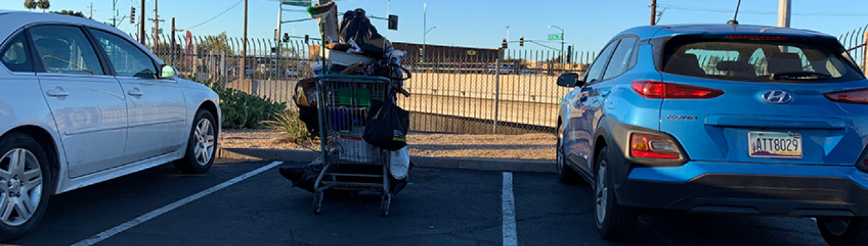 a shopping cart overflowing with miscellaneous items is parked between two cars