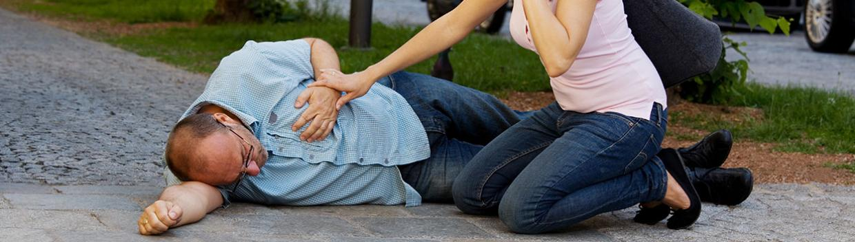 A man, on the ground, lies on his right side while a woman uses her cell phone