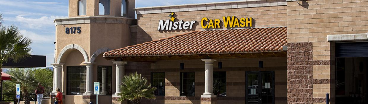 "the sign on a brown stone building reads ""Mister Car Wash"""