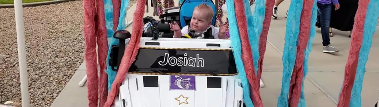 Toddler drives an adapted toy vehicle through a pretend car wash.