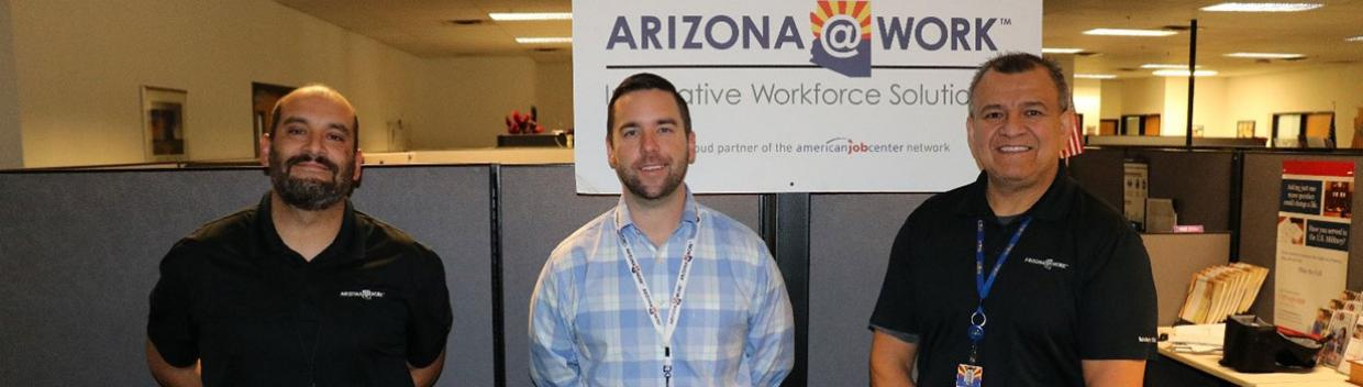 three men stand inside an office; in the background, an ARIZONA@WORK sign and cubicles are visible
